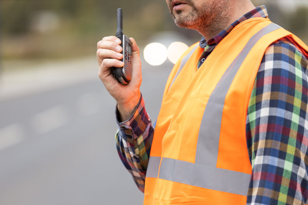 Road construction workers talking to walkie-talkie